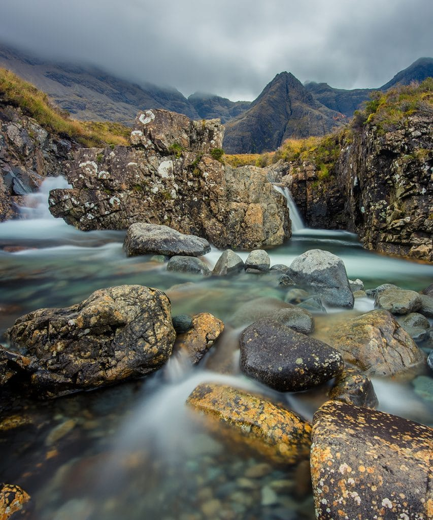 The fairy pools of Skye are visited by Scottish tours. The crystal clear mountain pools lie in front of the dramatic Black Cuillin Mountains.