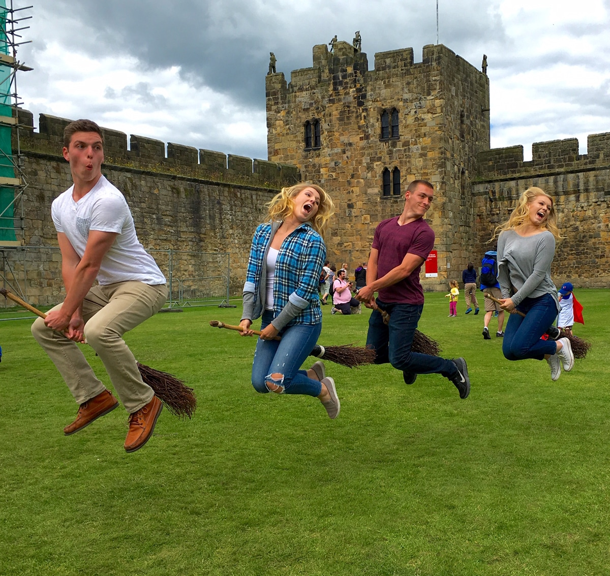 4 people jump in the air,pretending to fly broomsticks at Alnwick Castle